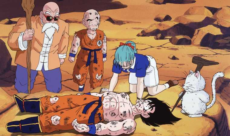 Goku lies defeated and battered, surrounded by friends